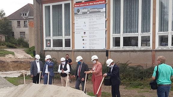 Mehrere Menschen mit Bauhelmen stehen hinter einem Sandhaufen vor einem Gebäude.