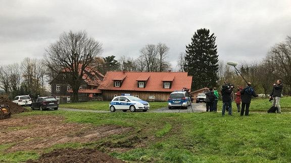 Zwei Polizeiautos und mehrere Reporter sowie ein Kamerateam stehen vor dem mit Holzbrettern verkleideten Wohnhaus des Thüringer AfD-Vorsitzenden Björn Höcke in Bornhagen im Eichsfeld