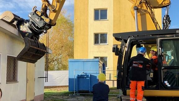 Ein Bagger setzt am Dach eines Gebäudes an.