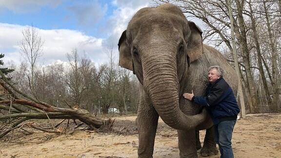 Ein Mann streichelt einen Elefanten.