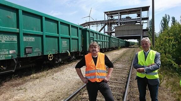 Zwei Männer in Schutzwesten neben einem Güterzug