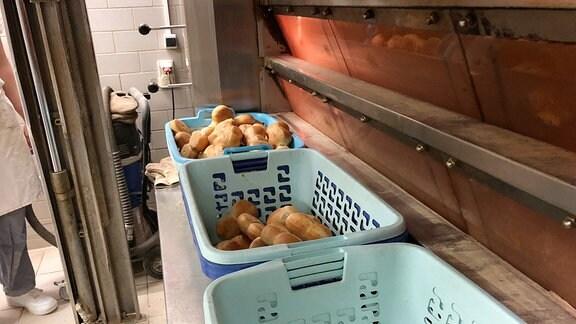 Brötchen liegen in Wäschekörben in einer Bäckerei