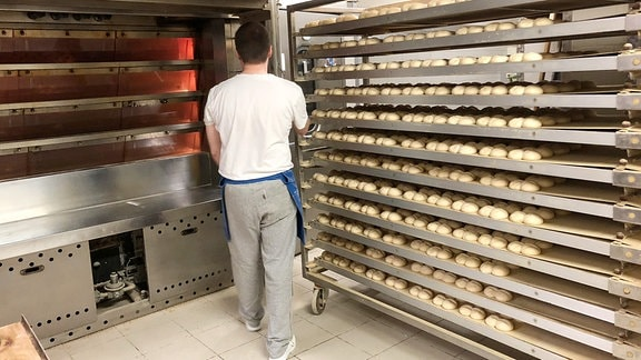 Bäcker mit noch ungebackenen Brötchen vor einem Backautomaten