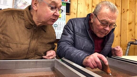 Stefan Franke und Manfred Schmidt gucken in die Brutrinne und suchen vom Pilz befallene Eier
