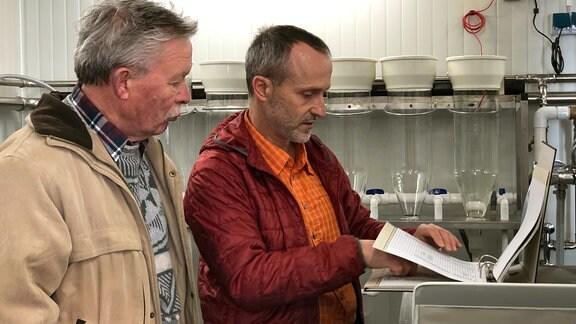 Die Angler Werner Schumann und Knuth Herrmann werfen einen prüfenden Blick auf Tabellen