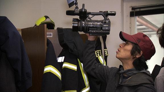 Ein Feuerwehrmann aus Japan mit einer Kamera in der Hand vor Feuerwehrmann-Schutzanzügen.
