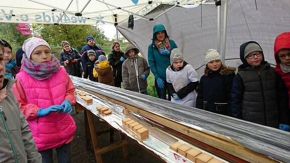 Zahlreiche Kinder stehen neben einem Tisch, auf dem eine mit Alufolie ausgeschlagene Dachrinne und Kekse liegen