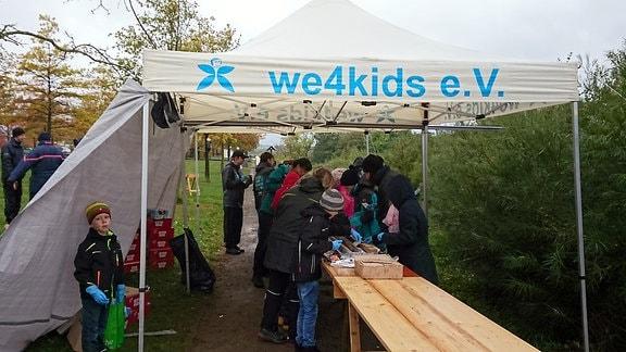 Mehrere Kinder stehen unter einem Pavillon an einem Holztisch
