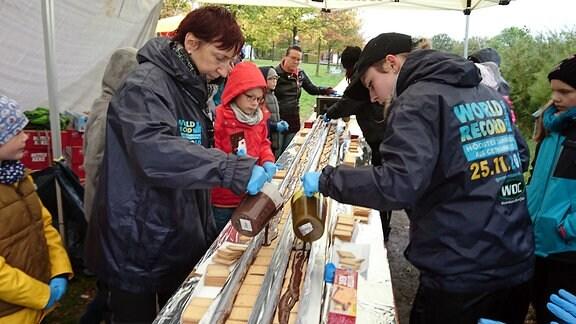 Zwei Frauen gießen flüssige Schokolade über Kekse, die in einer mit Alufolie ausgeschlagene Dachrinne liegen, daneben stehen einige Kinder