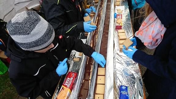 Kinder legen Kekse auf Schokolade, die in einer mit Alufolie ausgeschlagene Dachrinne ist