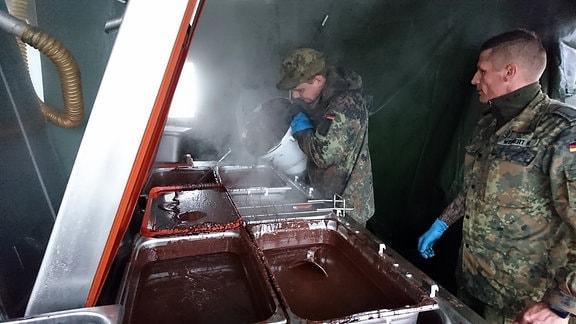 Zwei Soldaten in Uniform stehen in einer Großküche in einem großen Zelt neben flüssiger Schokolade