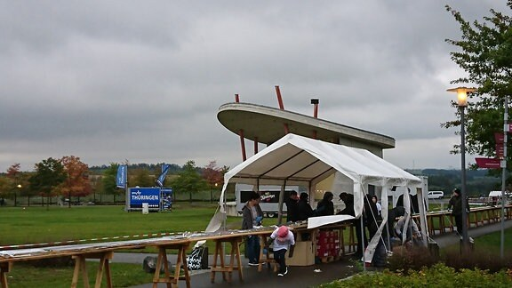 Mehrere Personen stehen unter einem Pavillon an einem Holztisch