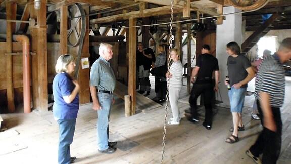 Besucher stehen in einer Mühle