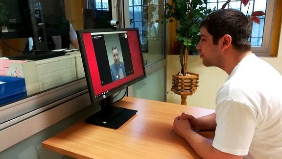 Ein Mann schaut in einen Computerbildschirm und telefoniert via Video mit einem anderen Mann