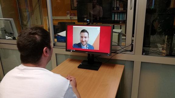 Ein Mann schaut in einen Computerbildschirm und Videotelefoniert via Skype mit einem anderen Mann