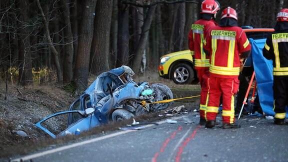 Das Wrack eines Autos im Straßengraben nach einem Unfall mit einem Bus zwischen Weida und Greiz