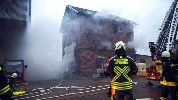 Feuerwehrmänner nähern sich einem Haus, aus dem Qualm dringt
