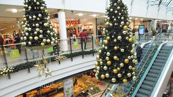 In einem Shopping-Center in Greiz mit mehreren Geschäften hängt noch vor dem Advent weihnachtliche Dekoration mit geschmückten Weihnachtsbäumen, die über einer Rolltreppe hängen