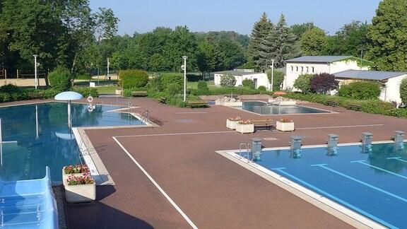 Schwimmbecken mit Rutsche und Liegemöglichkeiten sowie einem Beach-Volleyballfeld.
