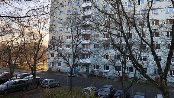 Ein 11-stöckiges Haus mit parkenden Autos davor