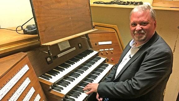 Ein Mann sitzt an den Tasten einer Orgel und guckt in die Kamera