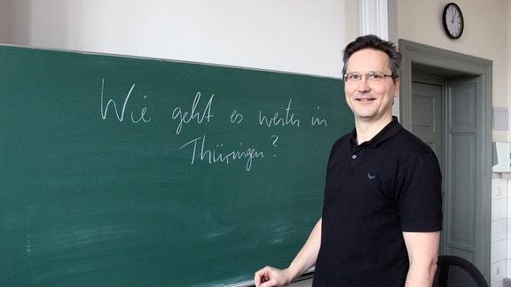Ein Lehrer steht vor einer Tafel.
