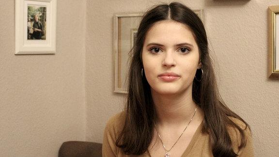 Eine Schülerin steht vor einer Wand mit Bildern.
