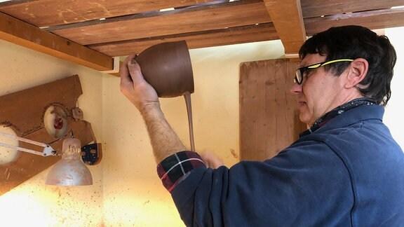 Keramiker Hendryk Fröderking setzt Henkel an Tontopf