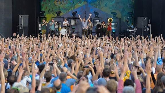 Konzert von LaBrassBanda bei der Kulturarena 2019 in Jena: Das Publikum jubelt und streckt die Hände in die Höhe.