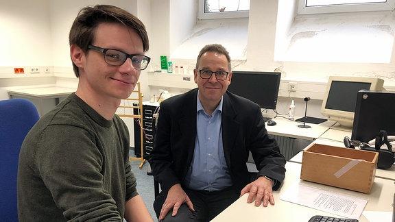 Doktorand Paul Winkler und Wahrnehmungsforscher Prof.Dr. Stefan Schweinberger sitzen an einem PC.