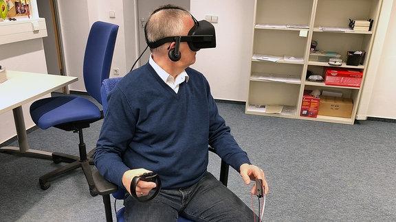 Ein Mann hat eine Virtual Reality Brille auf und sitzt in einem Labor.