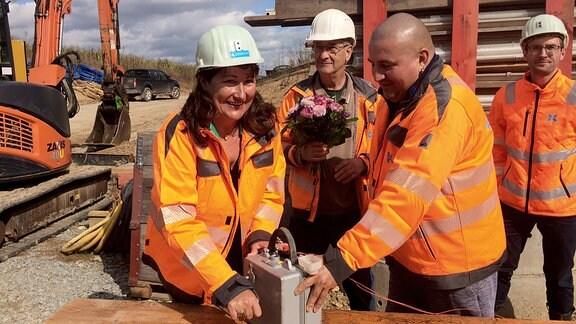 Eine Frau und drei Männer in orange-farbenen Sicherheitsjacken stehen auf einer Baustelle vor einer Metall-Box. Die Frau dreht an einem Hebel an der kleinen Metall-Box.