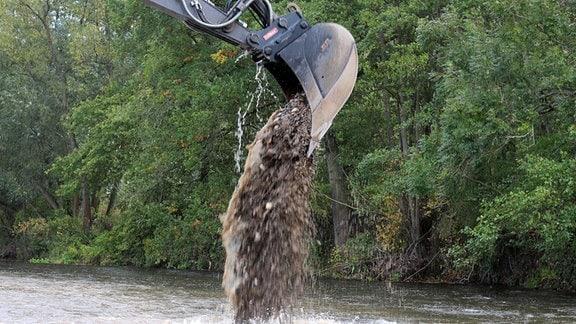 Ein Bagger schüttet Kies in einen Fluß.
