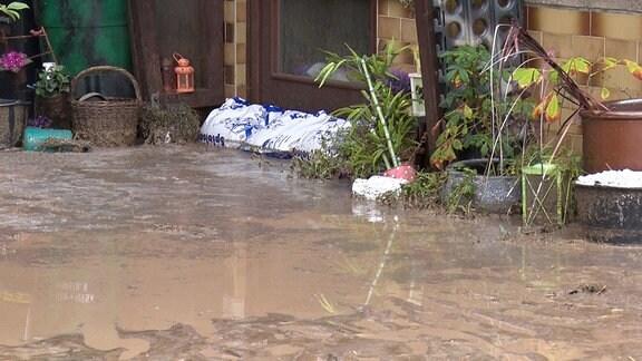 Wasser steht vor einer Haustür.