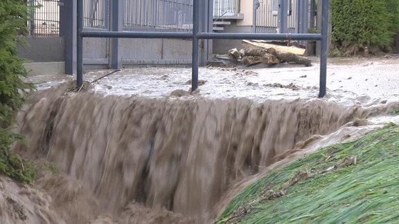 Schlammiges Wasser stürzt eine Kante herunter.