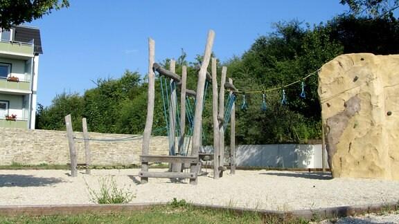 Der Blick fällt auf eine Konstruktion zum Klettern. Diese beginnt linksseitig mit aus krumm gewachsenen, bearbeiteten Baumstämmen und Seilen gefertigten Klettermöglichkeiten. Rechtsseitig anschließend ist eine sandfarbene Kletterwand. Im Hintergrund sieht man Gebüsch sowie links einen dreigeschossigen, grünen Wohnblock mit Balkons