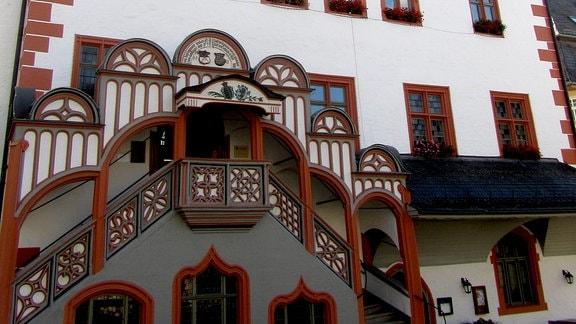 Ein reichhaltig verziertes Rathaus mit rot-braunen Elementen und heller Fassade. Die Treppe erstreckt sich über die Hälfte der Hausfassadeund ist reich verziert sowie überdacht. Rechts am Gebäude ist eine Uhr in die Dachform eingepasst. In der Dachmitte ist eine kleine Loggia. Die zahlreichen kleinen Fenster sind mit Blumen geschmückt