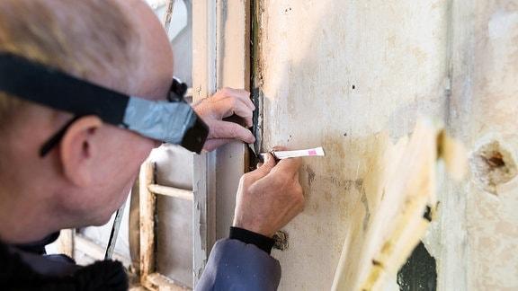 Ein Restaurator untersucht mit einem Skalpell eine Türzarge.