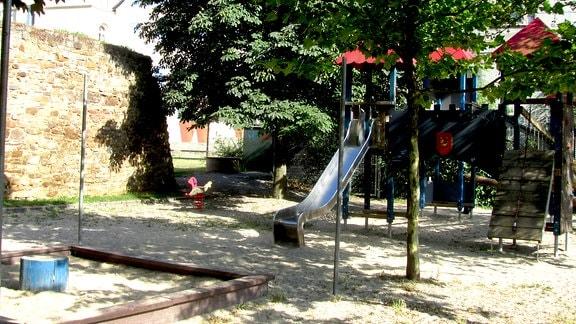 Ein Spielplatz. Links daneben eine Mauer aus Feldsteinen. In der Mitte, dahinter und vereinzelt auf dem Spielplatz stehen schattenspendende Laubbäume. Im Vordergrund links ist ein in Holzbohlen eingefasster Sandkasten. Im hinteren Bereich des Platzes findet sich ein Kletterturm sowie eine Rutsche