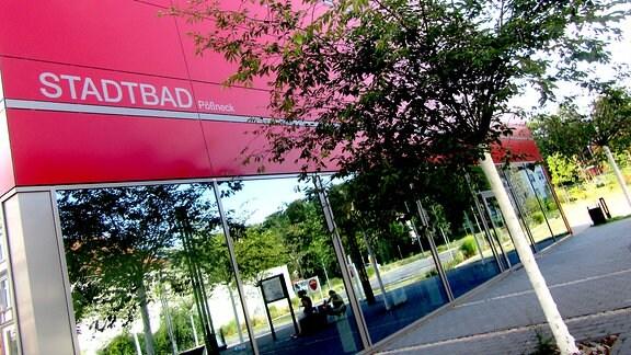"""Diagonal über die ganze Fläche des Bildes ist das moderne quadtratische Gebäude. Im unteren Bereich ist das Gebäude vollverglast. Im Glas spiegeln sich der Vorplatz des Bades. Eine Frau sitzt dort auf einer Bank, eine weitere befindet sich in der Hocke neben der Bank. Der obere Bereich des Gebäudes ist in einem kräftigen rot gehalten, zweimal unterbrochen durch graue Zierleisten. Links steht der Schriftzug """"Stadtbad Pößneck"""". Vor dem Gebäude befindet sich ein gepflasterter Parkplatz mit zwei kleinen Bäumen. Im hinteren Bereich ist ein Mülleimer."""
