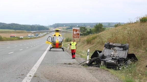 Ein Rettungshubschrauber steht auf der Autobahn. Im Graben liegt ein verunfalltes Auto auf dem Dach.