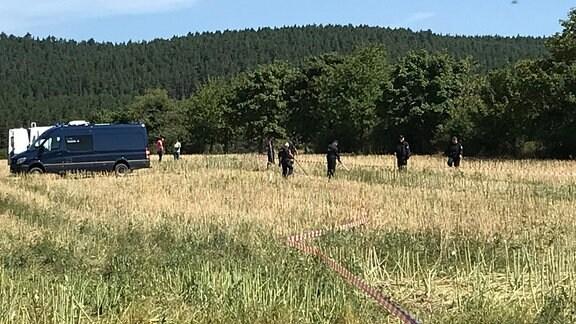 Mehrere Polizeibeamte stehen auf einem Feld. Das Gebiet ist mit Polizeiband abgesperrt.