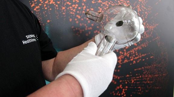 Röntgen-Röhre wird von einer Person mit beiden Händen gehalten. Dabei trägt diese Person weiße Handschuhe.