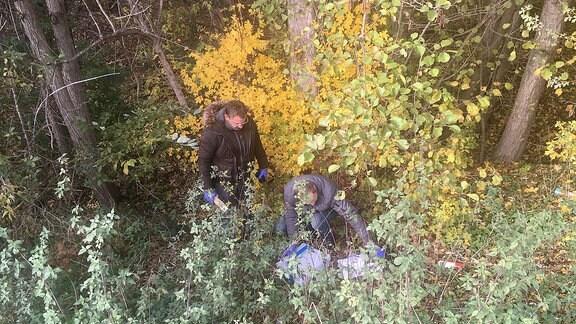 Zwei Männer suchen im Unterholz nach Spuren.
