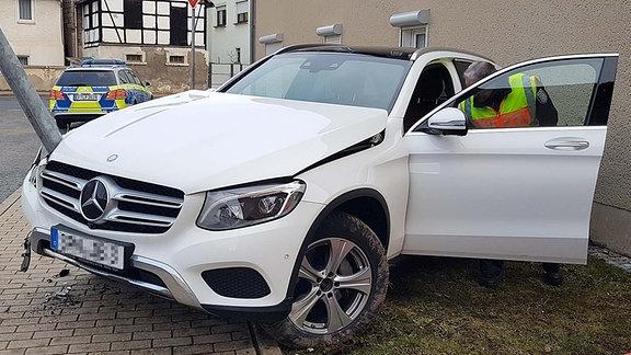 Ein weißer Mercedes SUV steht beschädigt an einem Laternenmast.