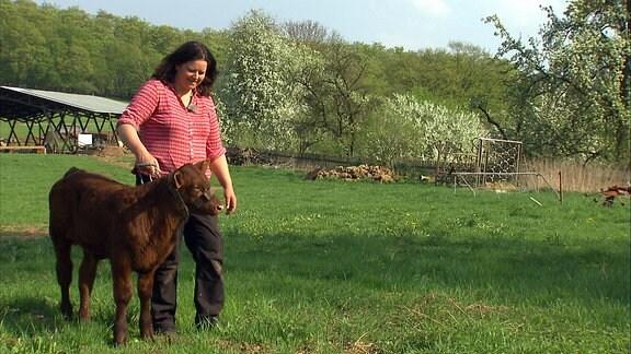 Eine Frau mit einem Harzer Höhenvieh-Kalb