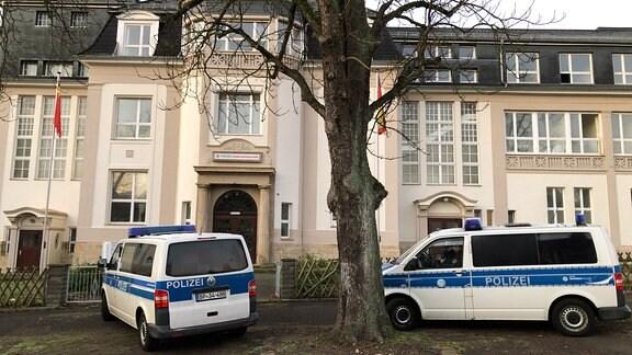 Polizeifahrzeuge vor einem Gebäude