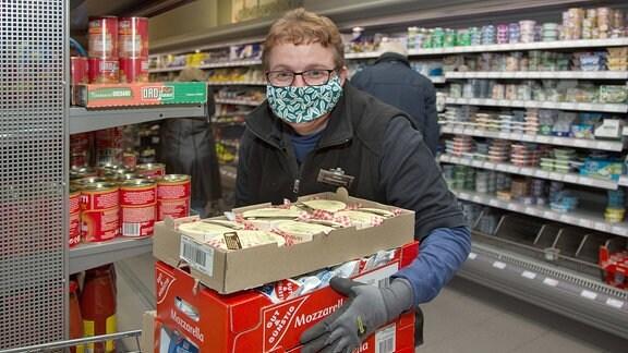 Frau mit Mundschutz beim Regale einräumen im Supermarkt