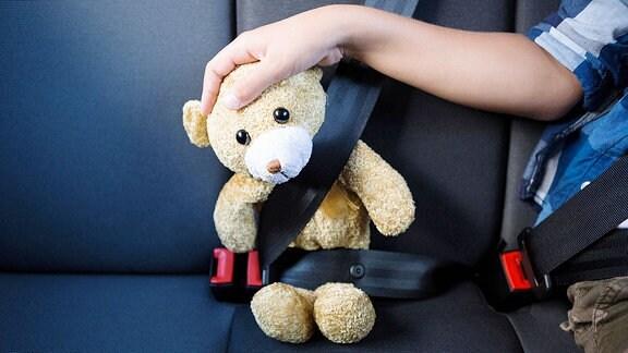 Ein Kind und ein Teddy sitzen angeschnallt im Auto.