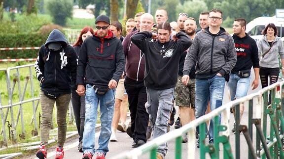 Mehrere Menschen laufen über einer mit Gittern abgesperrten Straße